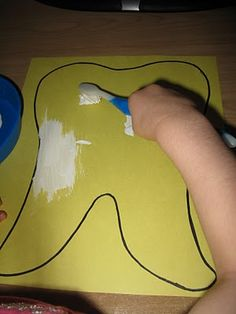 "Tooth art, painting a yellow tooth with white paint (""toothpaste"") and a toothbrush for a paintbrush."