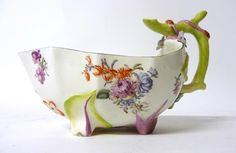 A Chelsea Porcelain Strawberry Leaf Sauce Boat, Red Anchor period, circa 1756, moulded with naturalistic leaves and branches picked out in colours and painted with scattered flowersprays and sprigs, red anchor mark