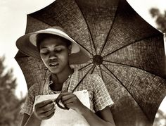 """July 1937. Louisiana. Medium-format nitrate negative and caption by Dorothea Lange for the Farm Security Administration. """"I'd be hard pressed to name a favorite among Lange's work, but this would be near the top. I love the reflected light on the woman's face, the few beads of sweat, the wonderful textures of the hat and the umbrella."""""""