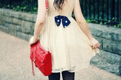 Very cute white flowy dress with the bright red shoulder purse.