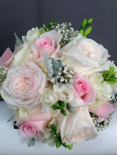 White O'Hare and Pink roses, white freesia, baby's breath, and dusty miller leaves make a beautiful bride bouquet.