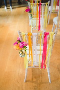 Colourful streamers chair decor with a glass vase and colourful flowers decorating each chair.  http://mackphotography.co.uk/