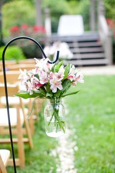 Alstroemeria in jars hanging from shepherds' hooks: inexpensive outdoor aisle decor