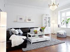 O sofá preto contrasta com o branco das paredes e das almofadas, conferindo sofisticação a um ambiente mais simples - Via ArtKasa