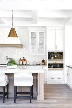 Gray striped upholstered counter stools sit at a gray wash wood island topped with a white quartz countertop illuminated by Goodman hanging Lamps hung from a white coffered ceiling.