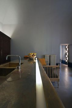 Interesting lighting  Modern minimal kitchen with long concrete countertop in modern apartment in Italy