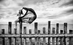 """""""Gerade als mein Model sich auf die Pfahlreihe im Bodensee setzte, überraschte sie ein Windstoß – und ich hatte das Glück, genau diesen Moment einzufangen.""""      Mehr Fotos vonSchamanin derVIEW Fotocommunity    Aktionen und Informationen aus der VIEW Fotocommunity aufFacebook,Google+oderTwitter"""