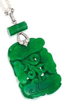 An Art Deco Platinum, Jadeite and Diamond Pendant, by Marcus & Co., Circa 1930. The rectangular carved and pierced jadeite plaque measuring approximately 47.2 by 32.3 by 7.8 mm, decorated with ru-yi symbols, topped by an additional jade cylinder, accented by old European and single-cut diamonds, signed Marcus, with indistinct numbering. #Marcus #ArtDeco #pendant