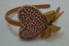 Tiara revestida em fita cetim dourada co lindo coração bordado em pérolas, strass e laço dourado.