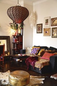 Bohemian Home That pendant lamp really makes the room. textiles, lamps, dark wood, art.