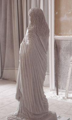 Vista perfil de pliegues ya tallados del manto recogido en brazo izquierdo