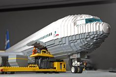 This is a scale model of a Boeing 777-200LR airliner. I built two cargo doors, which made for a convenient way of installing the threaded rod. But I also came up with a neat solution to hide the rod, which is actually encapsulated by the cab of the loader vehicle. An Air Canada baggage handler actually pointed out my model is missing an optional small cargo door at the rear of the plane.