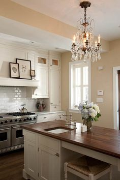 Love the dark walnut!  source: Mahogany Builders  Elegant kitchen design with white cabinetry and large island. Carrerra marble perimeter counters and stained dark walnut island counter. Beveled subway tile backsplash, Viking range and crystal and iron chandelier.   Restoration Hardware latte.