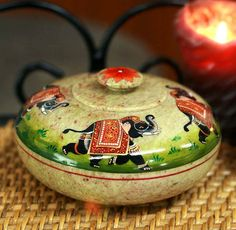 """Royal Fortune: Hand Crafted Soapstone Lidded Bowl (Medium)  Carved from natural soapstone, Royal elephants parade proudly around the lid, and a flower crowns the knob. Artisan paints the motifs by hand in the detailed style of India's traditional miniature paintings.  Product Code : BX-14  Size: 2.8"""" H x 5"""" Diam.  Weight: 1.6 lbs"""