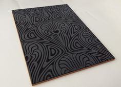 An Art Nouveau design engraved onto a black ceramic glazed tile