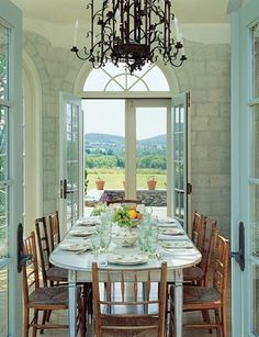 Beautiful dining room with Trompe L'oeil walls painted to look like stone, and plentiful glass French doors and arched transom windows