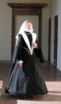 A Spanish mourning garment according to the Juan de Alcega's pattern book (1580) is characterized by a tight front and loose back half, below which lies the auxiliary lacing. The sleeves are typical Spanish pear-shaped sleeves. Clothing is complemented by a silk cap with a long veil, ruff and jewelry.