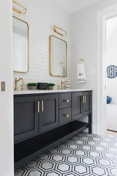 Black and gray marble floor tiles lead to a black wooden dual bath vanity boasti. Black and gray marble floor tiles lead to a black wooden dual bath vanity boasting a slatted shelf and a white marble countertop holding antique brass. Bathroom Floor Tiles, Bathroom Wallpaper, Boy Bathroom, Tile Floor, 2nd Floor, Wall Tiles, Modern Bathroom, Bad Inspiration, Bathroom Inspiration
