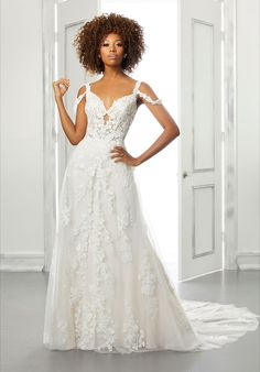 This whimsical wedding gown features floral appliques, a sculpted v- neckline with a split front skirt and a sheer lace train.