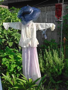 Gardens Inspired: Create a scarecrow    This is not my scarecrow - yet - but I think a visit to a thrift store for a ruffled blouse & floral skirt is in order to capture this same look -  I will have to look for THE hat there as well !  If I cannot find a black one then I will spray paint one black !!!!!