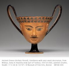 """Kantharos with satyr mask decoration. Ancient Greek, Archaic period from Miletus, Ionia in Anatolia (now part of Turkey), 550–525 BCE. Painted ceramic, H: 17.3 cm (6 13/16"""") 