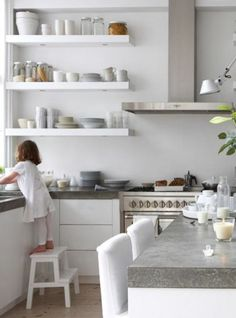 white kitchen with thick concrete-looking countertops.