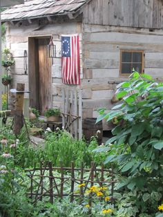 Rustic Log Cabin Shed...with flag...twiggy fence...flower garden...