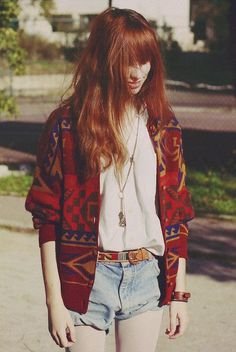 oversized light v neck tee half tucked into loose light wash short shorts, pendant necklace, reddy tribal print cardigan and belt, frizzy red hair with streaks of blonde and blunt bangs