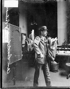 Portrait of a letter carrier standing in a Chicago office on Valentine's Day in 1911. He is carrying a double pack of mail to compensate for the increase in mail due to the holiday.