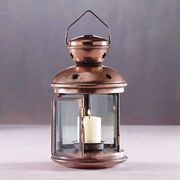 """$7.99 Colonial Lantern - Our very popular candle lantern can be used in a variety of settings.  This one is white but there are others in metallic finishes.   Has clear glass panels, star cutouts in the top and it even has a handle.  Candle cup is 1"""" across.  Metal and glass.  5"""" diameter x 9 1/2"""" high."""