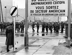 A West German policeman in the foreground left, watches a long row of East German National People's Army soldiers guard construction workers in the background, narrowing a border crossing at the sector border wall at Friedrich Strasse on Monday, December 4, 1961 in Berlin, Germany. (AP Photo) PA-11324438