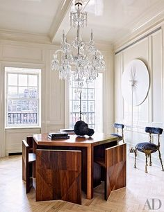 """A Baccarat chandelier glitters above a table and chairs in this bright entry 