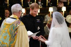 Prinssi Harry ja Meghan Markle pujottavtat vihkisormukset toisilleen.