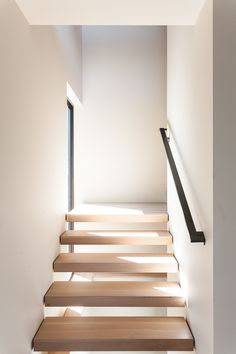 Custom solid ash floating stairwell, designed by Heliotrope Architects.