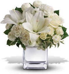 Surprise a faraway friend with this elegant array of Christmas flowers. White roses, lilies and other favorites are displayed in a chic mirrored silver cube. Simple and affordable, it is a lovely gift that will brighten spirits without breaking your bank.