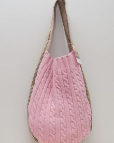 This pink upcycled tote is made of a pink cable knit sweater and features a long jute strap.