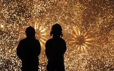 Las Fallas: Firefighters are silhouetted against exploding fireworks