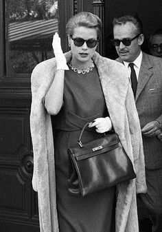 "Grace Kelly with her Hermès' leather bag still known today as the ""Kelly"" bag. She's also wearing one of her iconic styles (by Oliver Goldsmith?) of sunglasses."