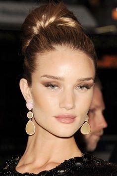 Rose Huntington-Whiteley opte pour un chignon plaqué boule sur le sommet de la tête. Mis en valeur par un maquillage féminine, cette coiffure réhausse ses traits et la rend très chic.
