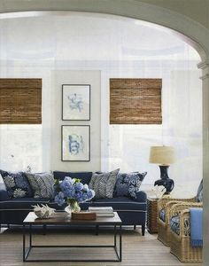 Blue and white family room with Seacloth pillows and Quadrille zig zag pillows on a blue sofa. Bamboo shades create a nice contrast in color and texture.