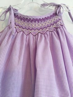 This size 1 dress is made of lavender gingham and yellow poly/cotton fabric. The front of the dress is smocked in lavender and yellow. The bottom of the dress has a yellow ruffle to match the smocking. The back is fastened with two heart buttons. French seams are included for Smocking Patterns, Baby Dress Patterns, Smocking Tutorial, Skirt Patterns, Coat Patterns, Blouse Patterns, Sewing Patterns, Smock Dress, Tie Dress