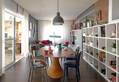 A sala de jantar tem mesa oval de Fernando Jaeger e cadeiras de diferentes estilos. A estante de nichos vazados de mesmo tamanho percorre toda a sala. Projeto da designer de interiores Carol Lovisaro, em parceria com a arquiteta Fernanda Lovisaro