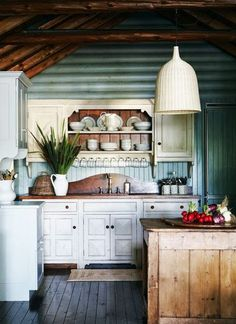Cozy log cabin kitchen with blue painted interior wood walls, white shaker cabinets and dark stained plank floors.