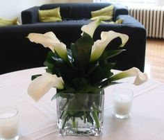 This is a cube vase floral arrangement featuring white, miniature calla lilies with dark green accents.  See our entire selection at www.starflor.com.  To purchase any of our floral selections, as gifts or décor, please call us at 800.520.8999 or visit our e-commerce portal at www.Starbrightnyc.com. This composition of flowers is generally available for same day delivery in New York City (NYC). SQ008