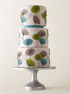 Very unique wedding Cake; the stylized flowers and color scheme give it a mid century modern feel.