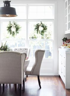 Chyka Keebaugh | © Toby Scott 15 | Est Magazine Dining Room with Upholstered chairs and green christmas decorations.  Industrial Lights