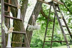Ceremony backdrop comprised of a chandelier & floral arrangements strung between two antique ladders.