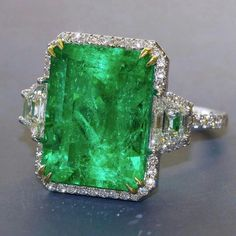 @dupuisauctions.Impressive Emerald ring of Colombian origin. Emerald is nearly 13.00 carats surrounded by small round diamonds and a pair of trapezoid-cut diamonds. estimates of $50,000-$60,000.