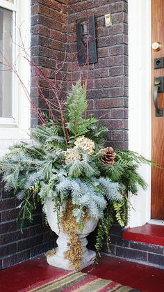 A wonderful way to greet your guests by placing an urn filled with a variety of fresh greenery by front door!