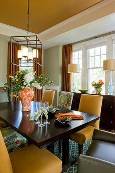 Interesting unexpected mix of chair fabrics - and orange vase centerpiece. Lamps on sideboard, cube chandelier, modern vs traditional table & chairs...